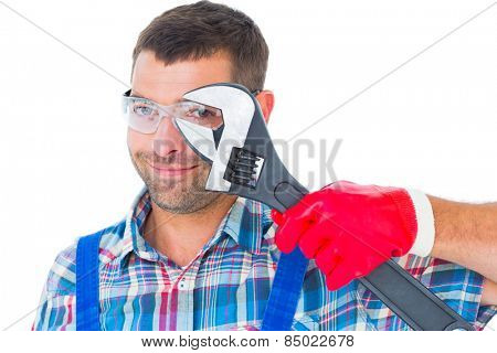 Portrait of confident repairman looking through adjustable wrench on white background