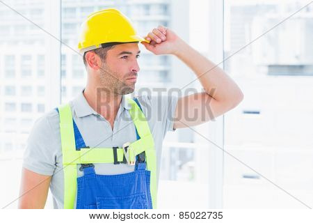 Portrait of manual worker wearing yellow hard hat in bright office