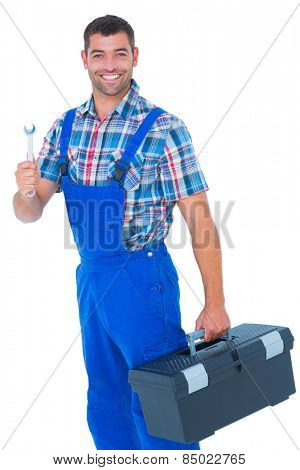 Portrait of smiling male repairman with toolbox and spanner on white background