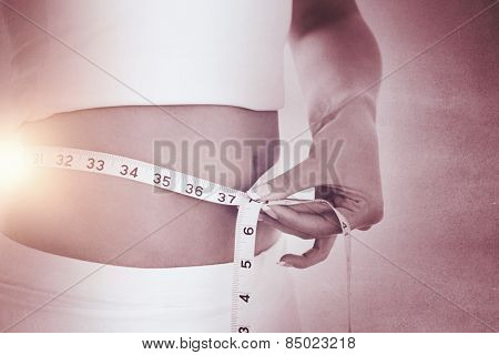 Closeup midsection of woman measuring waist against black wall