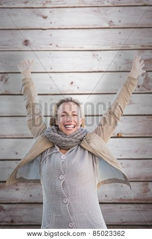 Cheering blonde against wooden planks