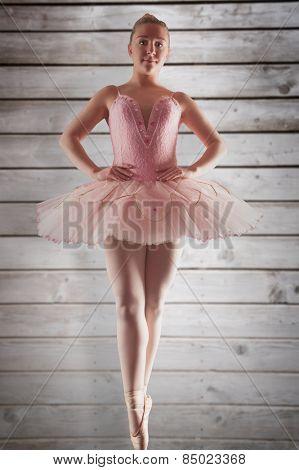 Pretty ballerina in pink standing en pointe against wooden planks