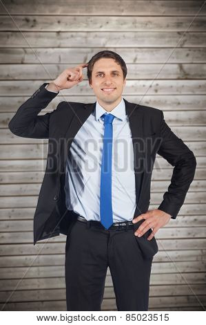 Thinking businessman scratching head against wooden planks background
