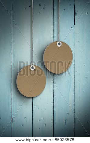 Circle tag hanging against painted blue wooden planks
