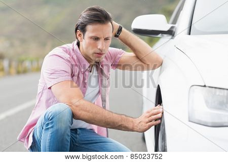 Stressed man looking at wheel of his car