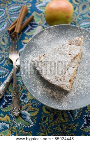A Piece Of Apple Pie Plate Lying On Gray, Cinnamon Sticks, Apple, Knife And Fork On Blue Background