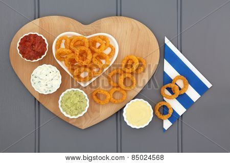 Onion ring snack food with dip selection and striped napkin.