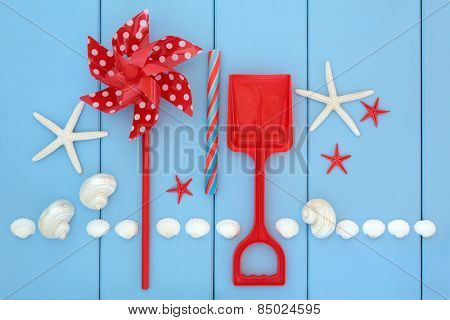 Toy windmill, spade, rock candy and sea shells over wooden blue background.