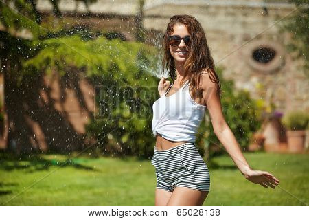 Beautiful young woman having fun in summer garden with garden hose splashing summer rain.