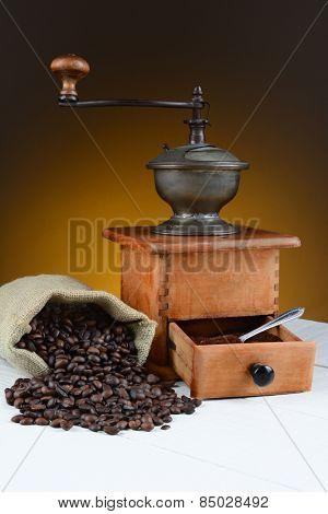 Coffee bean still life with antique grinder and spilled beans on a rustic wood table. Horizontal format with warm toned light to dark background..