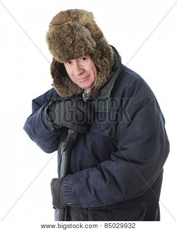 Close-up view of a happy senior man bundled for winter and leaning on a snow shovel's handle.  On a white background.