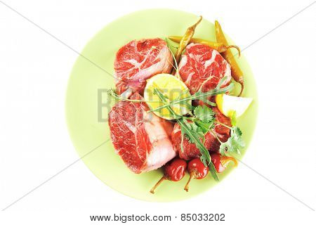raw beef meat medallion on green plate