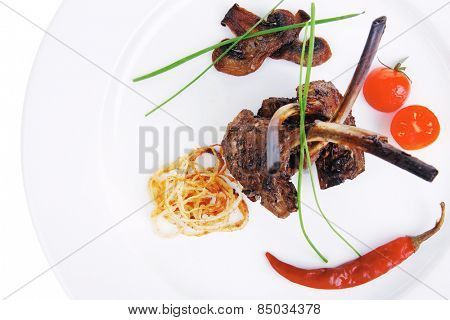 roast ribs with vegetables on white plate