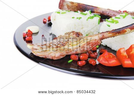 main course: grilled ribs with rice and tomatoes on black dish over white background . shallow dof