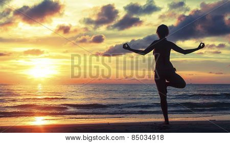 Silhouette of a woman practicing yoga during a beautiful sunset on the beach in subtropics.