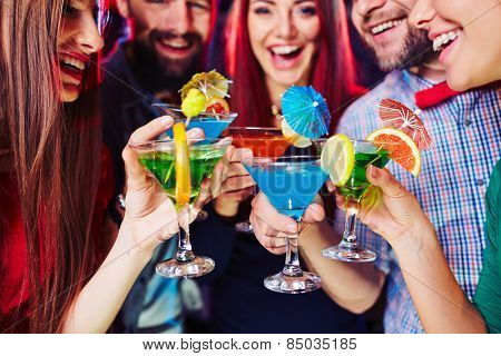 Young people clinking their cocktails