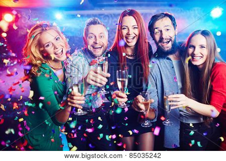 Young people with champagne flutes in confetti