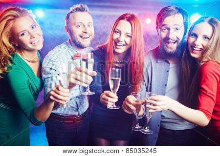 Portrait of young cheerful people with champagne flutes