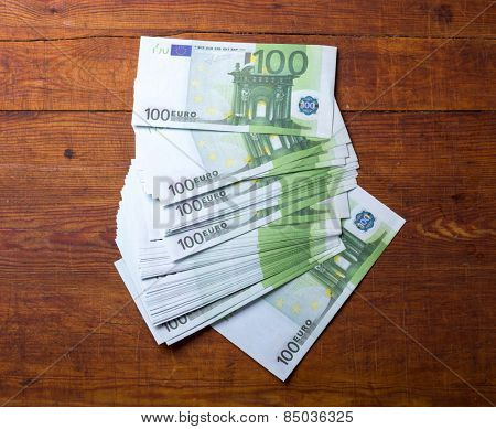 Close-up of  100 Euro banknotes on wood background.