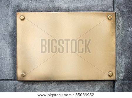blank gold or brass metal sign or nameboard on concrete wall