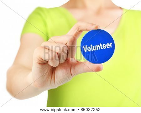 Round volunteer button in hand of girl isolated on white