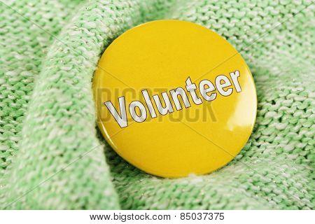 Round volunteer button on cloth background