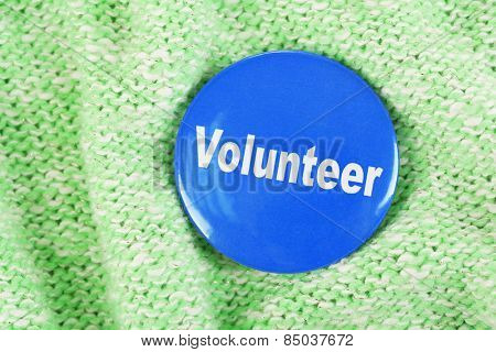 Round volunteer button on cloth background