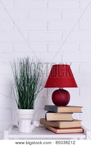 Interior design with lamp, plant, ceramic watering pot and books on tabletop on white brick wall background