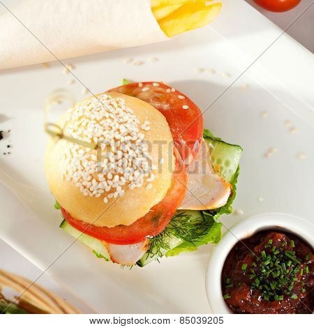 Sandwich with Smoked Meat, Tomato and Cucumber. Garnished with French Fries and Vegetables Sauce