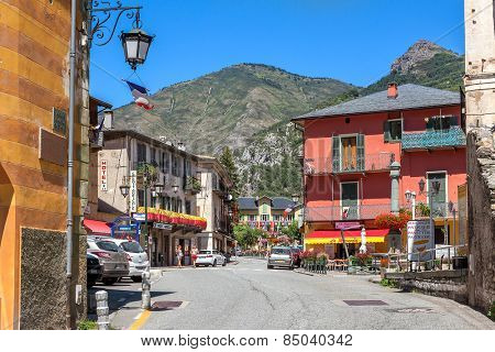 TENDE, FRANCE - AUGUST 12, 2014: Road among colorful houses in Tende - small town in French Alps located on old route of salt trade, popular with tourists and known for its cheese, honey and jams.