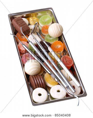 Dentist tools with sweets on tray isolated on white