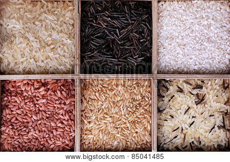 Different types of rice in box on wooden background