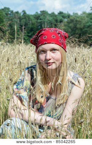 Blonde teenage girl sitting in cornfield