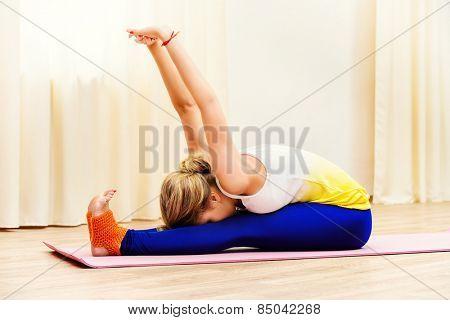 Slender athletic girl doing yoga exercises indoor. Stretching.