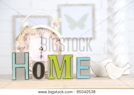 Home in colorful letters, in light white interior, on wooden shelf