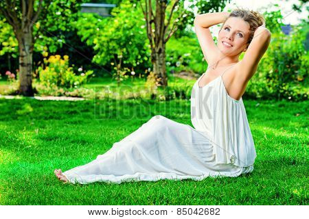 Beautiful smiling woman sitting on a grass outdoor. She is absolutely happy.