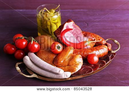 Assortment of deli meats on metal tray on color wooden background
