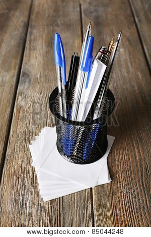 Different pens in metal holder with paper notes on wooden planks background