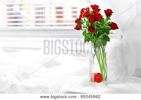 Bouquet of red roses in glass vase with heart on windowsill background