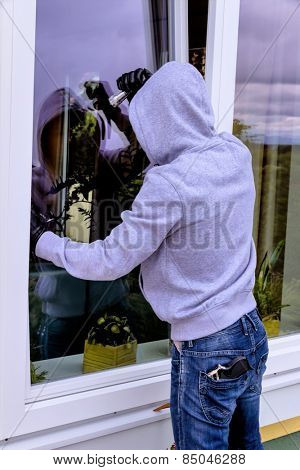 a burglar trying to break in an open window with a crowbar