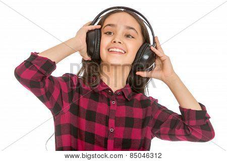 grins teen girl holding hands big black headphones worn on the h