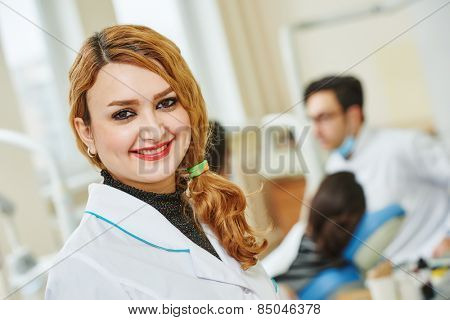 A portrait of a female dental assistant or doctor smiling the dentist working in the background