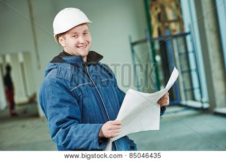 young male engeneer worker foreman at a indoors building site with blueprints