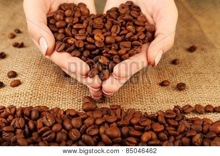 Female hands with coffee beans in shape of heart on burlap cloth background