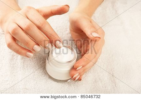 Female hand with cream on terry towel background