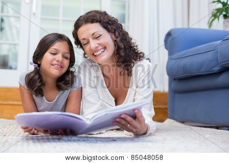 Happy mother and daughter lying on the floor and reading a book in the living room