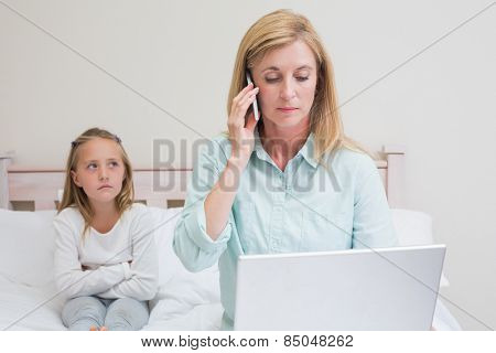 Mother ignoring her little girl in the bedroom