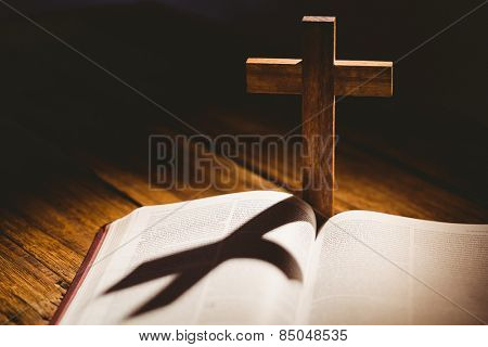 Open bible with crucifix icon behind on wooden table
