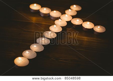 Candles in shape of cross on wooden table