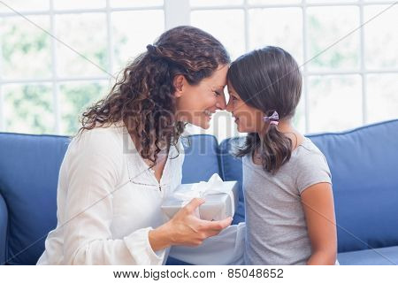 Cute girl offering gift to her mother in the living room